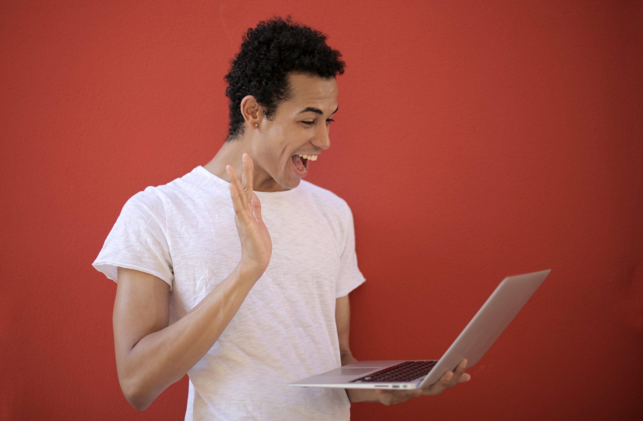 Person waving at laptop
